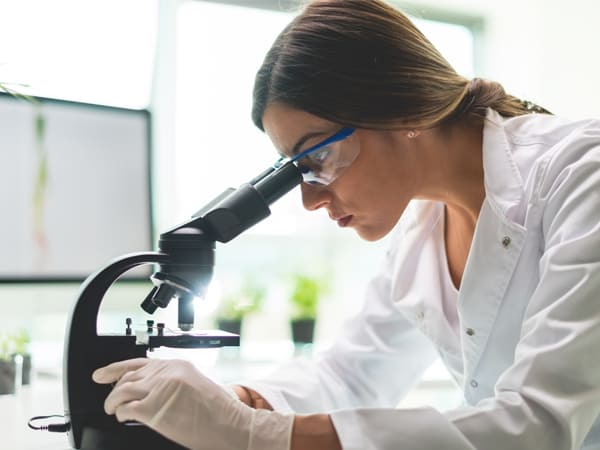 woman in lab coat looking through a microscope